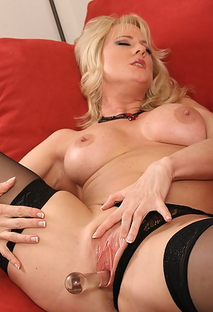 Blonde MILF with shaved pussy enjoying a glass dildo